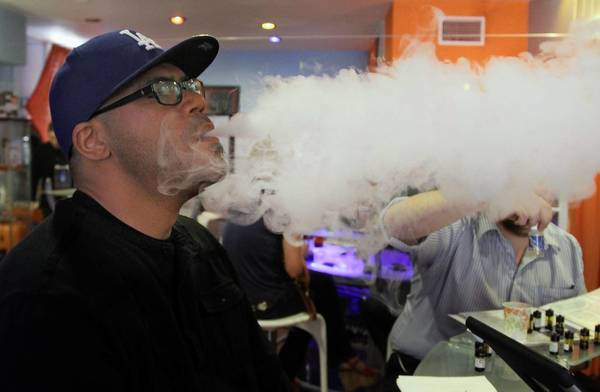 "Customer Eric Trotter ""vapes"" at the Vapor Spot in Westwood."