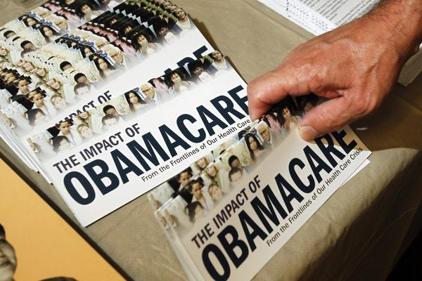 "A Tea Party member reaches for a pamphlet titled ""The Impact of Obamacare"", at a ""Food for Free Minds Tea Party Rally"" in Littleton, New Hampshire in this October 27, 2012 file photo."