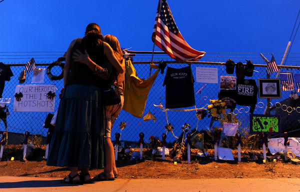 Two women console each other as they stand in front of a memorial in Prescott, Ariz. for the 19 firefighters killed.
