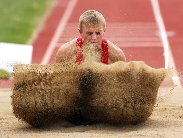 William Dougherty makes a splash in the sand as he competed in the long jump portion of the 17-18-year-old decathlon Thursday at the USATF Region 8 Junior Olympic Championships at Swisher Field.