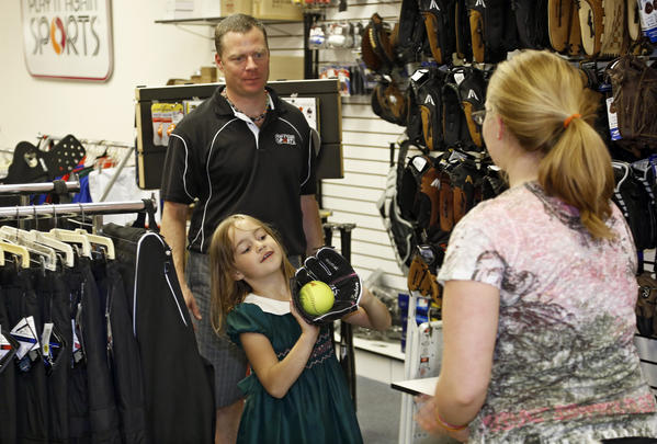 Chad Masters, back center, owner of Play It Again Sports, watches Abrianna Holler, 7, catch a ball tossed by Kinsey Town, right, as Abrianna tried out a baseball glove Tuesday.