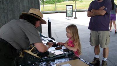 Park Ranger MaryJane Hartman shows Emma Schoenike, 4, casts of animal tracks on the new Childrens Discovery Table at the Flight 93 National Memorial. Emmas parents are Todd (in photo) and Tammy Schoenike of Minneapolis, Minn.