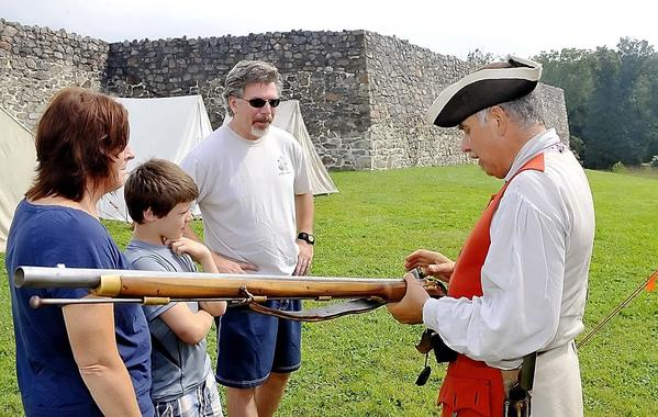 Kathy, Garrison and Joe Howell of Hagerstown listen to Dennis Kubicki of Mercersburg talk about his musket at Fort Fredrick.Fort Frederick presents activities from the daily life of French and Indian War soldiers, such as flag raising and lowering ceremonies and musket-firing practice. Special drills for children. 10 a.m. to 5 p.m. weekdays through Monday, Sept. 2