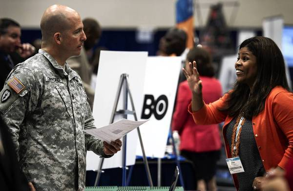 A soldier speaks with a job recruiter during the Hiring Our Heroes job fair in Washington, D.C. The job fair was held in conjunction with the annual convention of the National Cable and Telecommunications Assn., with dozens of telecommunications firms represented.