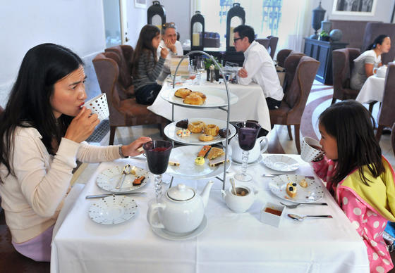 Catherine Mak and her daughter Lexi Mak, 7, of Grafton, Mass., enjoy afternoon tea at The Courtyard Restaurant at The Boston Public Library.