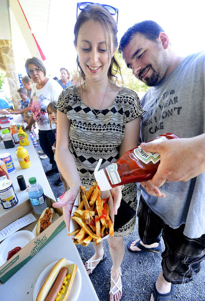 Nicole Petefish, left, holds fresh cut french fries as her fiance' Jeremy Vermillion pours on the ketchup Friday night during the Boonsboro Independance Day Celebration at Shafer Park.