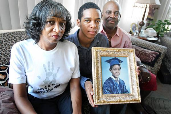 Rhonda Foster, her son, Alec, 16, and her husband, Ruett, pose with a framed portrait of Evan Foster in their Compton home. Evan, 7, was shot and killed at an Inglewood park in 1997. Rhonda Foster works with gang-prevention programs. Ruett Foster is a pastor and social worker. Together they make regular visits to local youth prisons, reaching out to troubled young men.