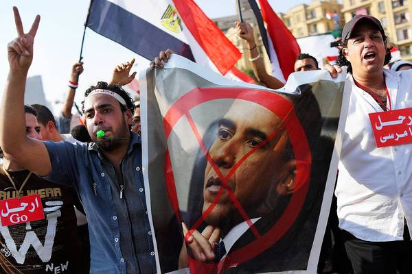 Egyptians carry anti-Obama posters as thousands of protesters celebrate in Tahrir Square this week. Each side in the toppling of President Mohamed Morsi accuses the U.S. of supporting the other.