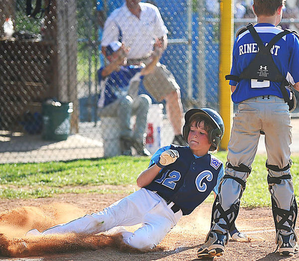 Conococheague's Kyle Hott slides into home plate past Valley catcher Dawson Rinehart on Friday during the Maryland District 1 10-11 championship game at Valley Little League.