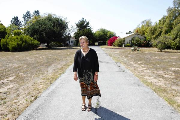 Kathy Anderson walks down the original driveway as she recalls living on the property of her family's 1940s home on Tustin Avenue in Costa Mesa.