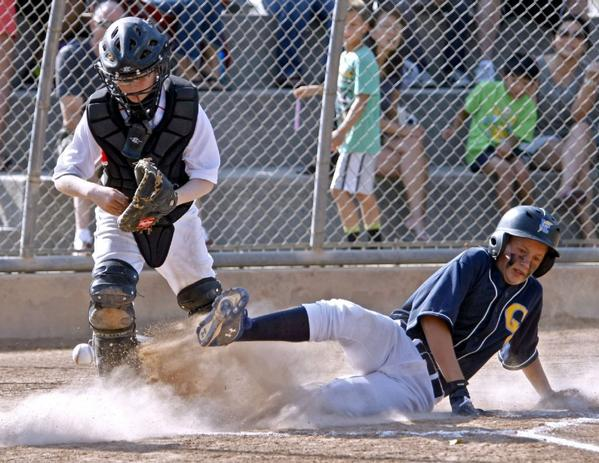Crescenta Valley's Braenden Bentzen, right, slides in safe as Foothill's catcher Andy Hovland goes for the ball.