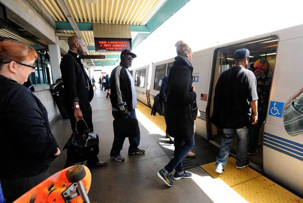Passengers board the first train headed into San Francisco at the West Oakland BART station on Friday. Commuter rail service resumed Friday after a five-day strike when workers' existing contract was extended to Aug. 4.