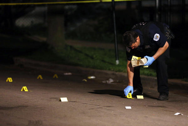 A Chicago police investigator places numbers on the bullet casings, at a crime scene where one man was shot in the 6400 block of S. Oakley Ave. on July 5.