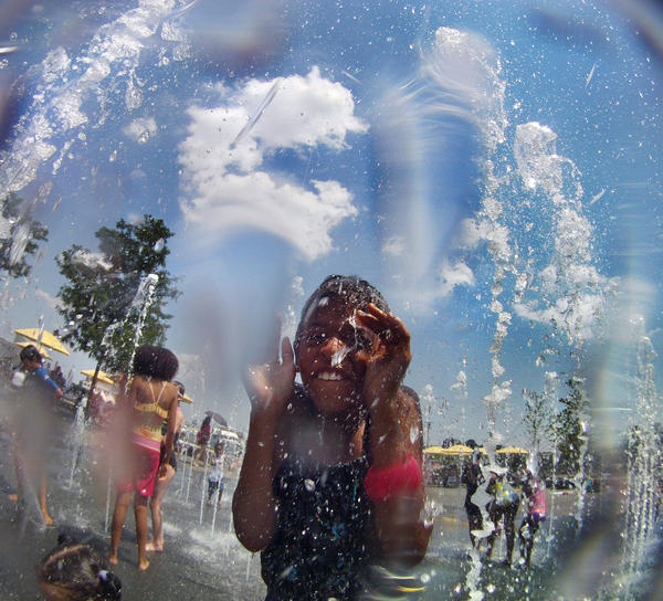 Tahnyah Gardner, 9 of Baltimore is surrounded by water spray, with visitors using the Walter Sondheim Fountain as relief from heat.