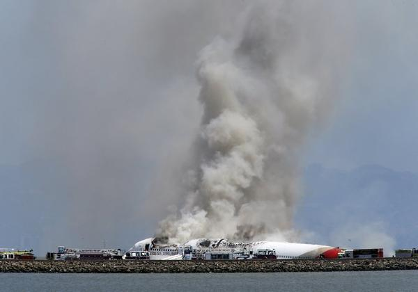 Smokes rises from Asiana Airlines Flight 214 after it crashed at San Francisco International Airport.