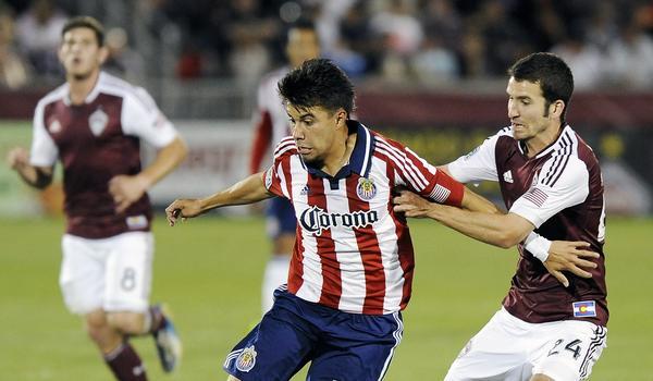 Chivas USA midfielder Carlos Alvarez battles with Colorado Rapids midfielder Nathan Sturgis during a 2-0 Chivas USA loss on May 25.