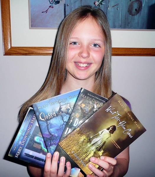 Stephanie Klemick, 10, of Emmaus, holds several books by one of her favorite authors, Mary Downing Hahn