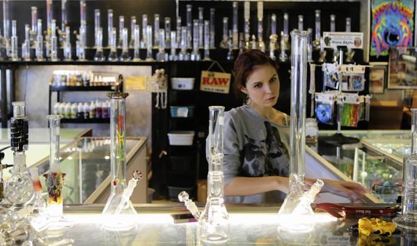 Brianna Howard, 21, sells water pipes and tobacco smoking paraphernalia at Mystik smoke shop in Orlando, Fla. Saturday, July 6, 2013.