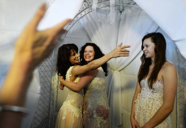 Andrea Taylor, left, hugs partner Sallee Taylor and reaches for Taylor's daughter, Grace Meier, 15, after the couple were married Monday in West Hollywood. For gay couples in states that don't recognize their marriages, however, a Supreme Court ruling leaves uncertainty about tax laws and other federal rules.