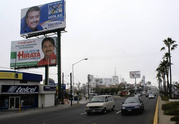 Campaign billboards tower over a road in Ensenada, in the Mexican state of Baja California, which will pick a governor Sunday. The National Action Party, which has held the Baja governorship since 1989, is in danger of losing the post to a candidate of the Institutional Revolutionary Party, a blow that could be irreparable to the party.