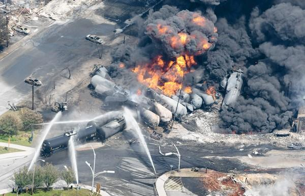 After a runaway train derailed in the center of Lac-Megantic, Quebec, smoke rises from tanker cars containing crude oil. A large swath of the town was destroyed and at least one person is dead and scores missing.