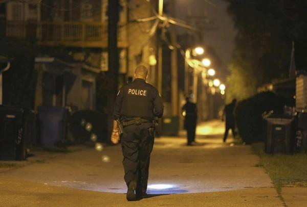 Police investigate an alley near Laramie and Adams, where a man was shot Saturday.