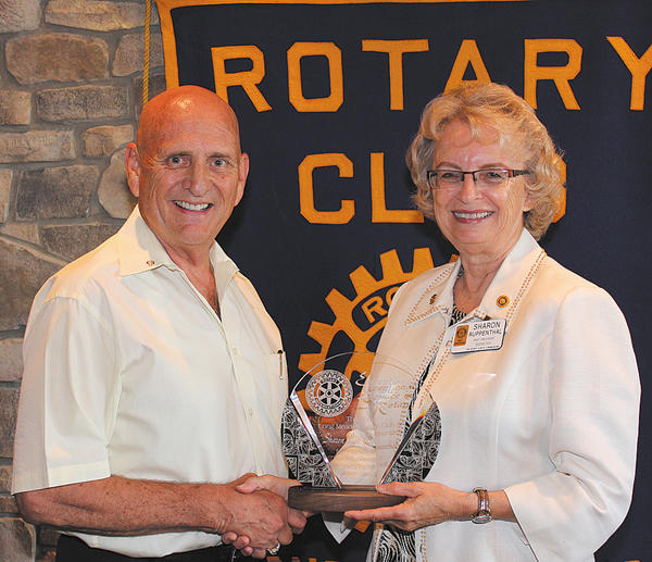 Rotary Club of Long Meadows Club President Ron Bowers presents Rotarian Sharon Ruppenthal with an award that highlighted her efforts during her 10 years as a Rotary member.