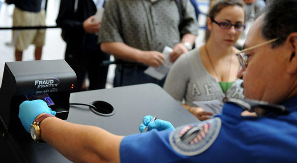 A TSA agent checks an id under a Fraud Fighter machine in Terminal 1 at LAX.