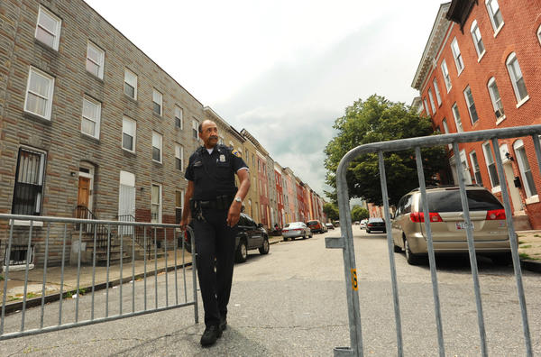 Baltimore Police Officer George Smith closes a gate at the mouth of the 900 block of Bennett Place after allowing a local driver to proceed down the street.