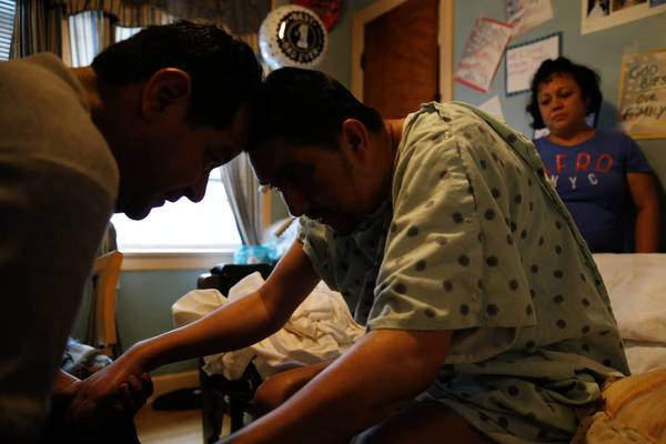 Jesus Arroyo, who does not have medical insurance, receives body massages and stretching exercises from self-taught physical therapist Jesus Vargas and Arroyo's wife, Ana Rodriguez. Arroyo, 38, is recovering from a 2011 accident that left him partially paralyzed.
