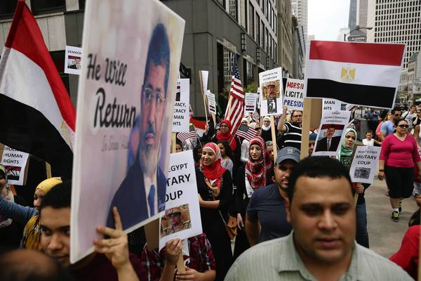 Protesters crowd Michigan Avenue during a pro-democracy rally Sunday in front of the Egyptian Consulate in Chicago.