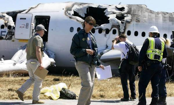 Officials with the National Transportation Safety Board inspect the site of the crash of Asiana Airlines Flight 214 at San Francisco International Airport.