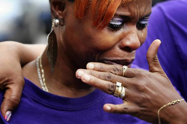 Debra Butler-Cureton cries after an anti-violence march Saturday in Englewood.