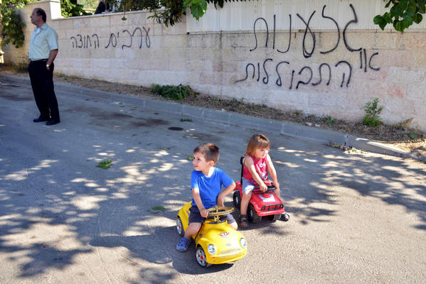 "An Israeli Arab man and children are seen on a street next to Hebrew graffiti that reads, ""Racism or assimilation"" and ""Arabs out"" on June 18 in the village of Abu Ghosh near Jerusalem. In an unrelated act that some attribute to racist attitudes, Israeli teenagers were sentenced Monday in the beating of an Israeli Arab youth in August 2012."