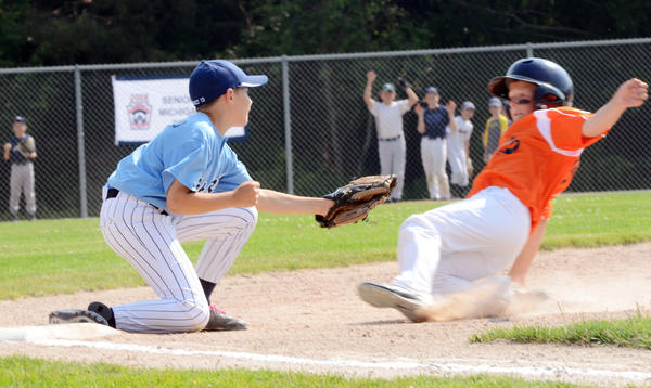 Petoskey third baseman Merrek de Castro (left) tags out Rogers City baserunner Jared Sharpe during a Little League District 13 Major Division (ages 11-12) pool play game Friday at Bates Field in Petoskey.