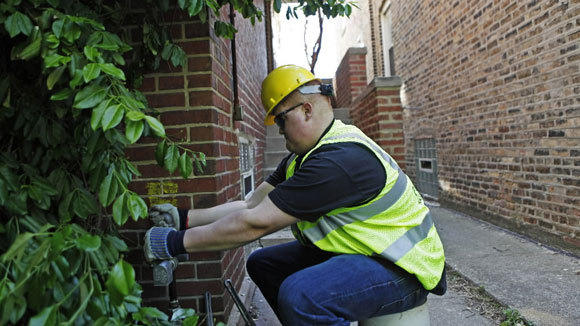 Joe Hilton installs a gas-pressure regulator outside a home on the 3400 block of North Harding Avenue in Chicago in April 2012.