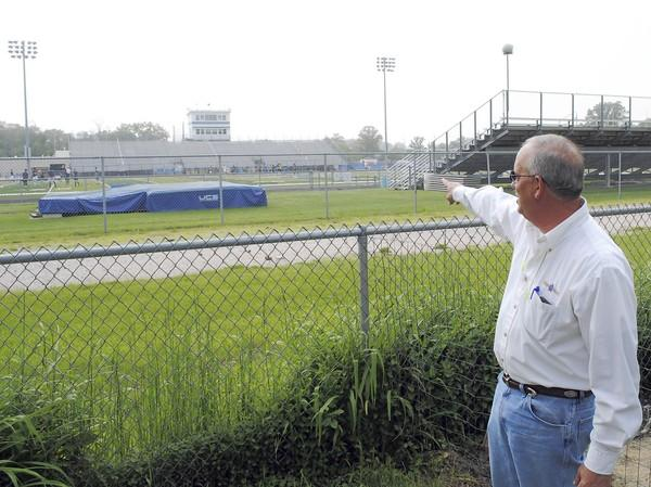 Kevin Fassett gestures across the fence in his yard, which looks out onto the 20 yard line of Wolters Field, where Highland Park High School plays its home football games, among other sporting events.