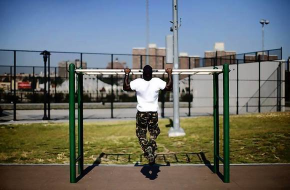 """A man works out in an outdoor """"Adult Playground"""" exercise area at Macombs Dam Park in the Bronx section of New York City."""