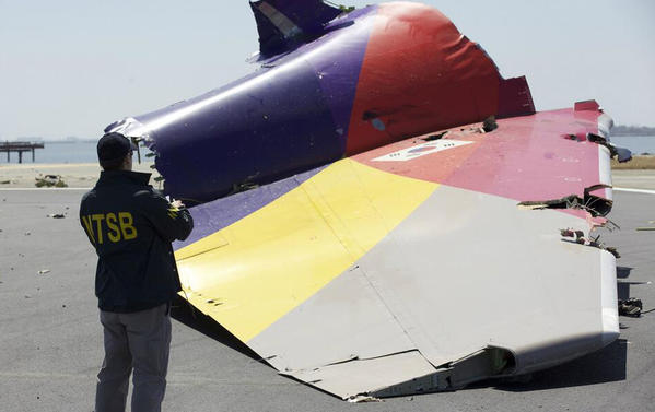 An NTSB investigator looks at the tail section of Asiana Flight 214 in San Francisco.