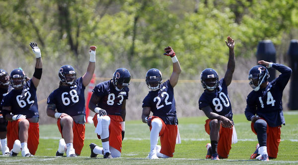 Martellus Bennett (83), Matt Forte (22), Earl Bennett (80) and the team stretch during a Chicago Bears organized team activity at Halas Hall.