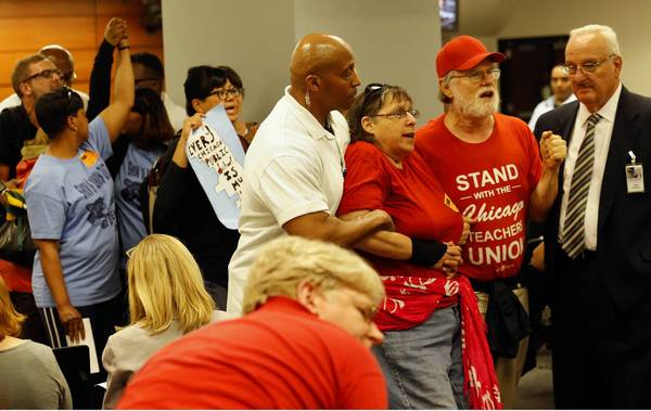 Protesters are escorted from the Chicago Board of Education meeting after disrupting the meeting on school closings.