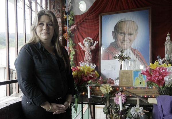 Floribeth Mora in front of a shrine to Pope John Paul II in Costa Rica. Mora was healed of a brain aneurysm, a cure that the Catholic Church is citing to advance John Paul II's path to sainthood.