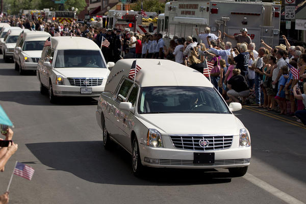 Hearses carrying the bodies of 19 firefighters killed last week arrive in Prescott, Ariz., during a procession that started in Phoenix.