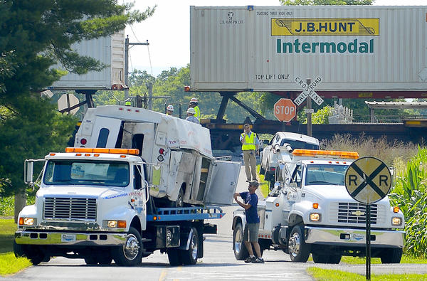 A work truck is lifted onto a flatbed truck after the work vehicle collided with a train Monday afternoon on Mason Road between U.S. 11 and Browns Mill Road.