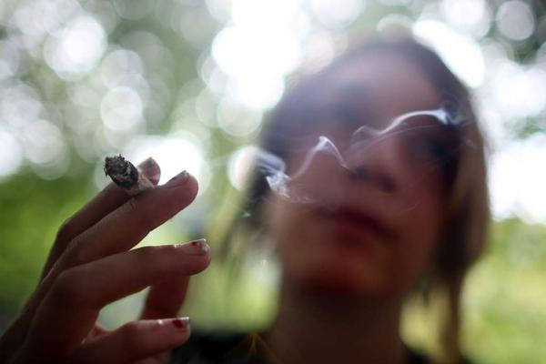 A woman smokes a cigarette in a New York park.