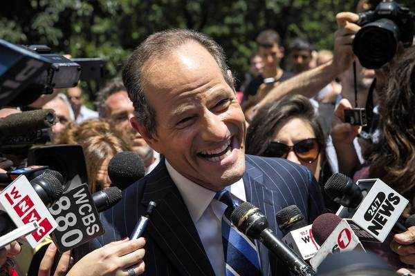Former New York Gov. Eliot Spitzer is mobbed by reporters Monday while attempting to collect signatures to run for comptroller of New York City.
