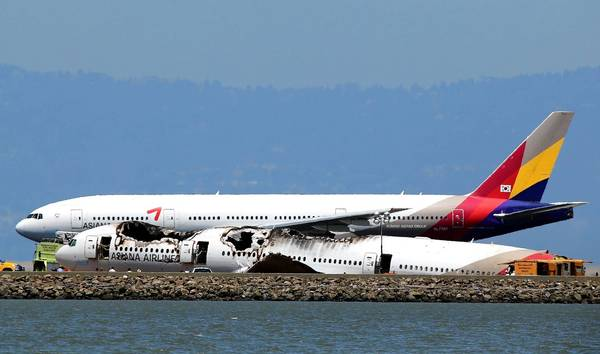 "An Asiana Airlines jetliner preparing to take off from San Francisco International Airport passes the wreckage of Asiana Flight 214. ""Both pilots should have seen that something was going wrong,"" said Barry Schiff, a TWA pilot for 34 years and now an aviation safety expert. ""Why didn't one of them say or do something?"""