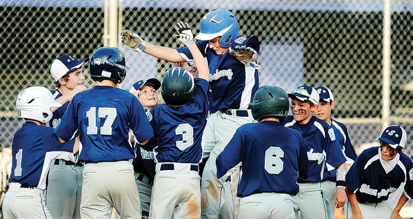 Sharpsburg's Ryan Nolan leaps above his teammates at home plate after hitting a home run in the third inning against Federal in Monday's Maryland District 1 11-12 losers' bracket final.