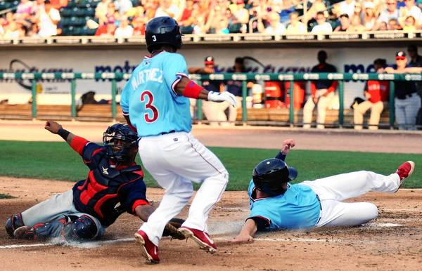 The IronPigs' Michael Martinez (right) and Steven Lerud (9) are safe at home as Pawtucket catcher Alberto Rosario is late with the tag.