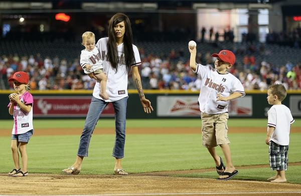 Juliann Ashcraft, wife of fallen Arizona firefighter Andrew Ashcraft, accompanies her children (from left to right) Shiloh, Choice, Ryder and Tate as they throw out the ceremonial first pitch before the start of Monday's Dodgers-Arizona Diamondbacks game.